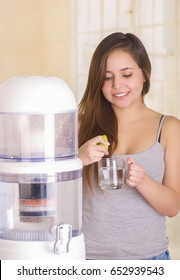 Beautiful smiling woman adding some lemon juice into the glass of water, filter system of water purifier on a kitchen background