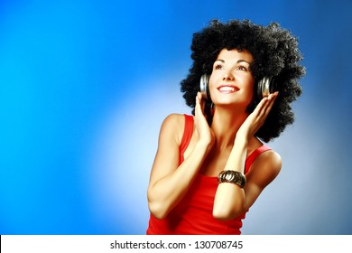 Beautiful smiling woman with afro hair listen to music with headphones on blue background