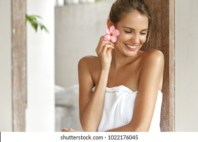 Beautiful smiling woman after bath covered by white towel, holds flower as had aromatherapy, looks thoughtfully and happily down, has fresh skin and perfect body. Cleanness and beauty concept