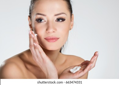 Beautiful smiling woman applying cream on face