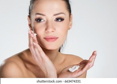 Schöne lächelnde Frau, die Creme im Gesicht aufträgt