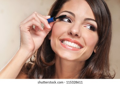 Beautiful smiling woman applying mascara on her eyelashes