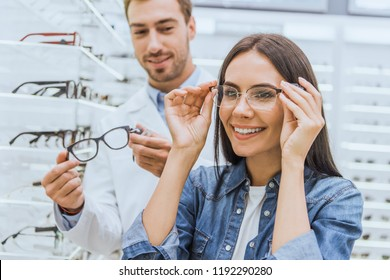 beautiful smiling woman choosing eyeglasses while male oculist standing near with another eyeglasses in ophthalmic shop