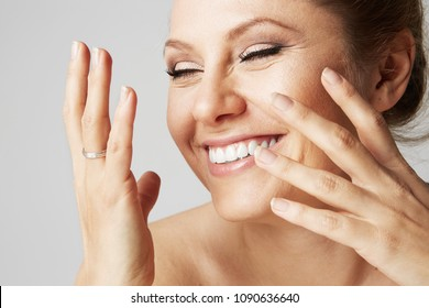 Beautiful smiling woman with clean skin, natural make-up, and white teeth on gray background. Close up portrait.Medical and cosmetic facial skin healthcare concept