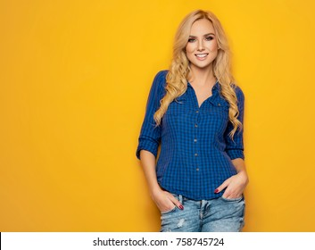 Beautiful smiling woman with clean skin, and white teeth posing on yellow background