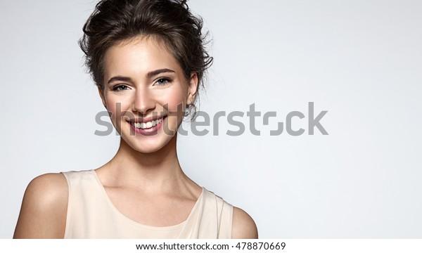 グレイの背景に清潔な肌、自然のメイク、白い歯を持つ美しい笑顔の女性