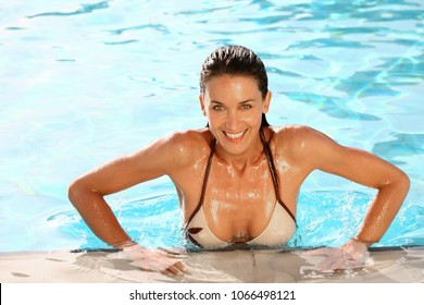 beautiful smiling woman coming out of a swimming pool