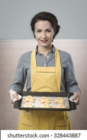 Beautiful smiling woman cooking gingerbread men cookies in a baking tray