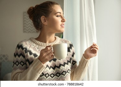 Beautiful smiling woman with cup of coffee near window