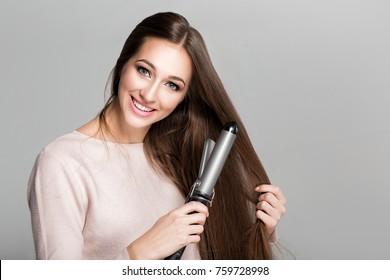 Beautiful smiling woman curling long hair using curling iron.