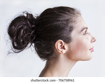 Beautiful Smiling Woman with Dark hair in Bun Hairstyle from Side view - Profile Portrait