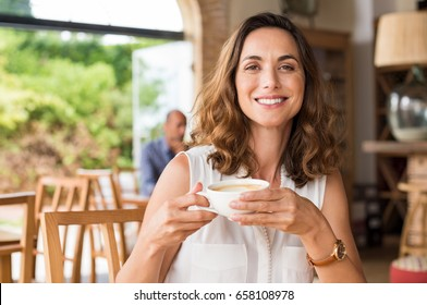 Beautiful smiling woman drinking coffee at cafe. Portrait of mature woman in a cafeteria drinking hot cappuccino and looking at camera. Pretty woman with cup of coffee.