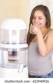 Beautiful smiling woman drinking a glass of water with a filter system of water purifier on a kitchen background