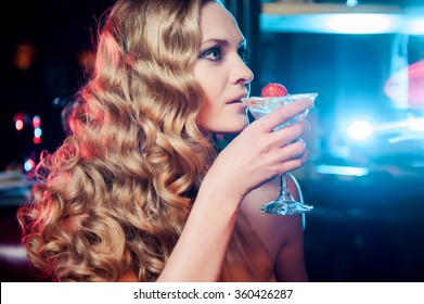 Beautiful smiling woman drinking martini at the bar