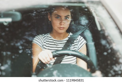 Beautiful smiling woman driving a car. Pretty girl sitting in automobile