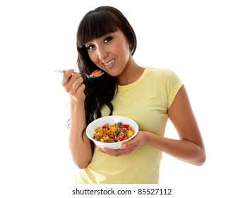 A beautiful smiling woman eating a healthy breakfast of cereals, nuts and fruit.  White background.