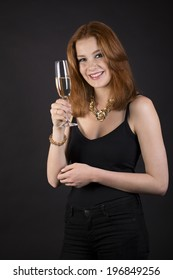 Beautiful smiling woman in elegant evening wear celebrating and toasting with a stylish flute of champagne against a dark background