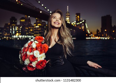 Beautiful smiling woman enjoy her birthday rose flower bouquet present at the party in the city