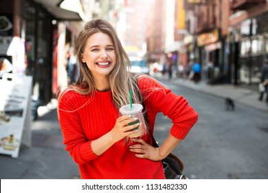 Beautiful smiling woman enjoy refreshment iced coffee drink on city street