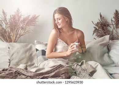 Beautiful smiling woman enjoying warm coffee in sunny apartment.Relaxation in bed.Sunny light warm home.Hygge scandinavian concept
