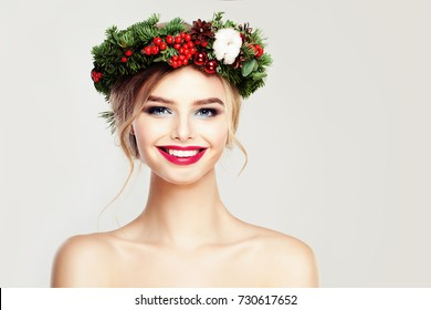 Beautiful Smiling Woman Fashion Model. Happy Girl with Christmas or New Year Wreath with Green Xmas Tree Twig, Red Decor and Berry. Cute Female Face Closeup