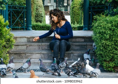 Beautiful smiling woman feeding pigeons in the park during the day