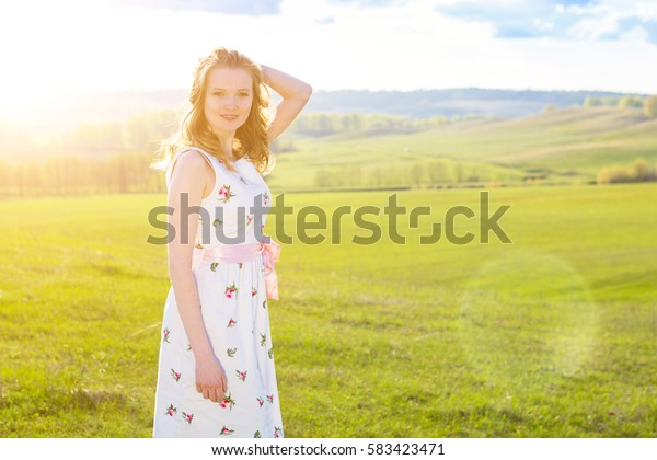 Beautiful smiling woman in a field at sunset. Beautiful Model girl in white dress on the Field.