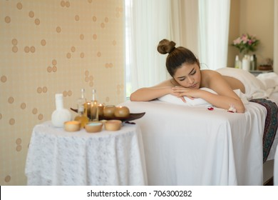 Beautiful smiling woman with flowers resting in the spa before massage.