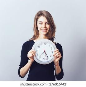 Beautiful smiling woman holding big clock.