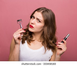 Beautiful smiling woman holding an eyelash curler