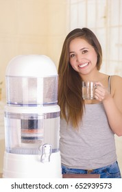 Beautiful smiling woman holding a glass of water behind of a filter system of water purifier on a kitchen background
