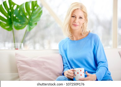 Beautiful smiling woman holding mug in her hand while sitting on sofa and relaxing at home.
