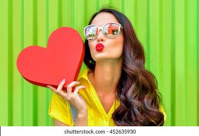 Beautiful smiling woman holding a red heart over green background. Fashion portrait stylish pretty woman in sunglasses outdoor.