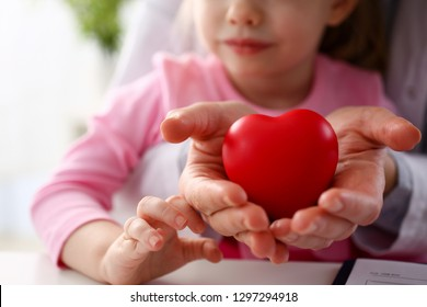 Beautiful smiling woman and kid hold red toy heart in arms closeup. Female give birth to life, palm hug diagnosis aid healthy pregnancy feel peace donation service souls together abortion
