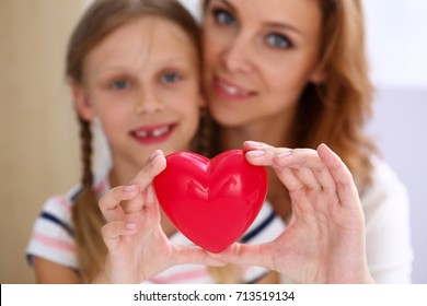 Beautiful smiling woman and kid hold red toy heart in arms closeup. Female give birth to life, palm hug, diagnosis aid, healthy pregnancy, feel peace, donation service, souls together, abortion