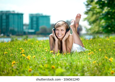 Beautiful smiling woman Woman listening to music on headphones outdoors