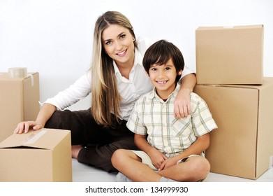 Beautiful smiling woman and little boy openig cardboard box
