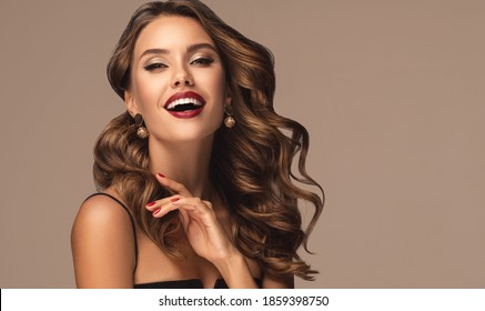 Beautiful smiling woman with long wavy hair .  Girl curly hairstyle  and red manicure nails . Beauty ,makeup and cosmetics . Earring jewelry