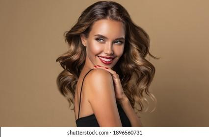 Schöne lächelnde Frau mit langwelligen Haaren.  Girl-Frisur und rote Maniküre. Schönheit, Make-up und Kosmetik.