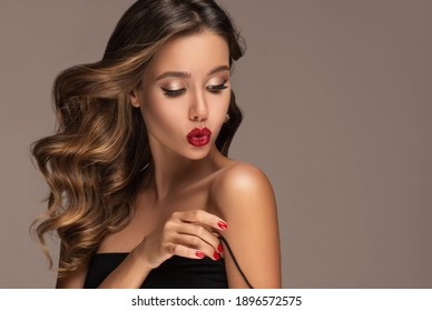 Beautiful smiling woman with long wavy hair .  Girl curly hairstyle  and red manicure nails .Clothes,makeup and cosmetics . The beauty straightens the strap on the dress.