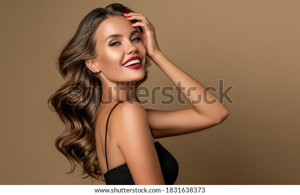 Beautiful smiling woman with long wavy hair .  Girl curly hairstyle  and red manicure nails . Beauty ,makeup and cosmetics .