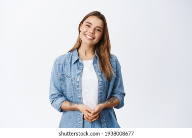 Beautiful smiling woman looking friendly and ready to help customer or client, holding hands together and staring at camera, white background