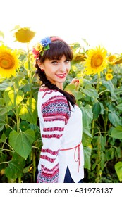 Beautiful smiling woman in national ukrainian blouse embrodery looking to camera on a sunflower field on sunset, backlight