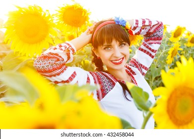 Beautiful smiling woman in national ukrainian blouse embrodery looking to camera on a sunflower field at sunset, backlight.