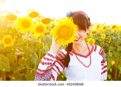Beautiful smiling woman in national ukrainian blouse embrodery holding a sunflower on a field at backlight