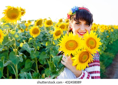 Beautiful smiling woman in national ukrainian blouse embrodery holding three sunflowers on a plant at sunset, backlight.