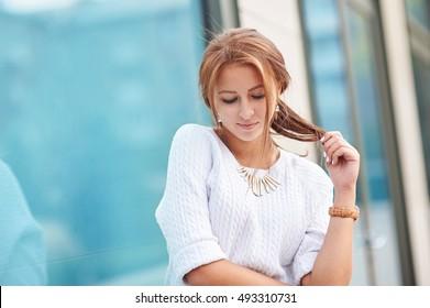 Beautiful smiling woman near the window on street