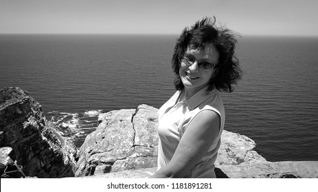 Beautiful smiling woman with ocean in the background. Black and White photography. Travel & Vacation. Sweet memories. Classic image. Old photo. Stunning retro photo. Nostalgia.