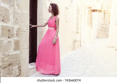 Beautiful smiling woman opening her house door outside. Fashionable long pink dress.