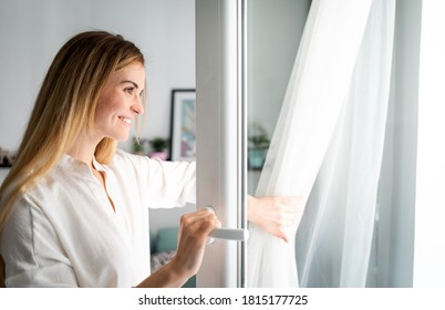 Beautiful smiling woman opening window at the morning
